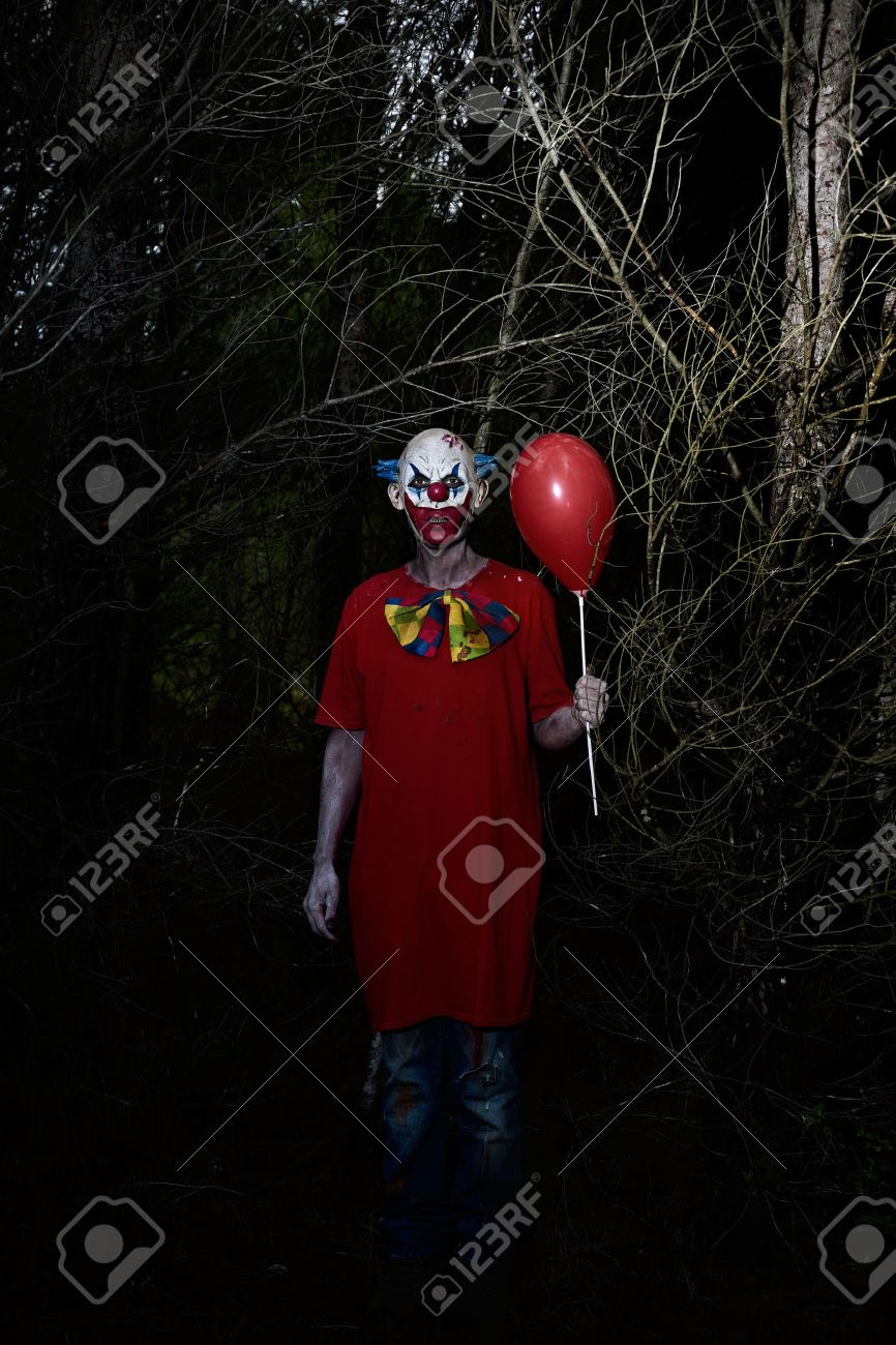 a scary evil clown wearing a dirty costume, holding a red balloon in his hand, in the woods at night - 71131893