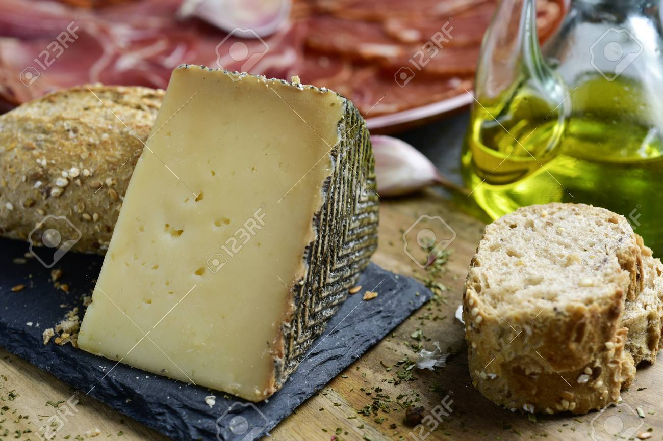 closeup of a piece of manchego cheese, some slices of bread, a cruet with olive oil and a plate with an assortment of different spanish cold meats as chorizo, cured pork tenderloin and serrano ham - 71168582