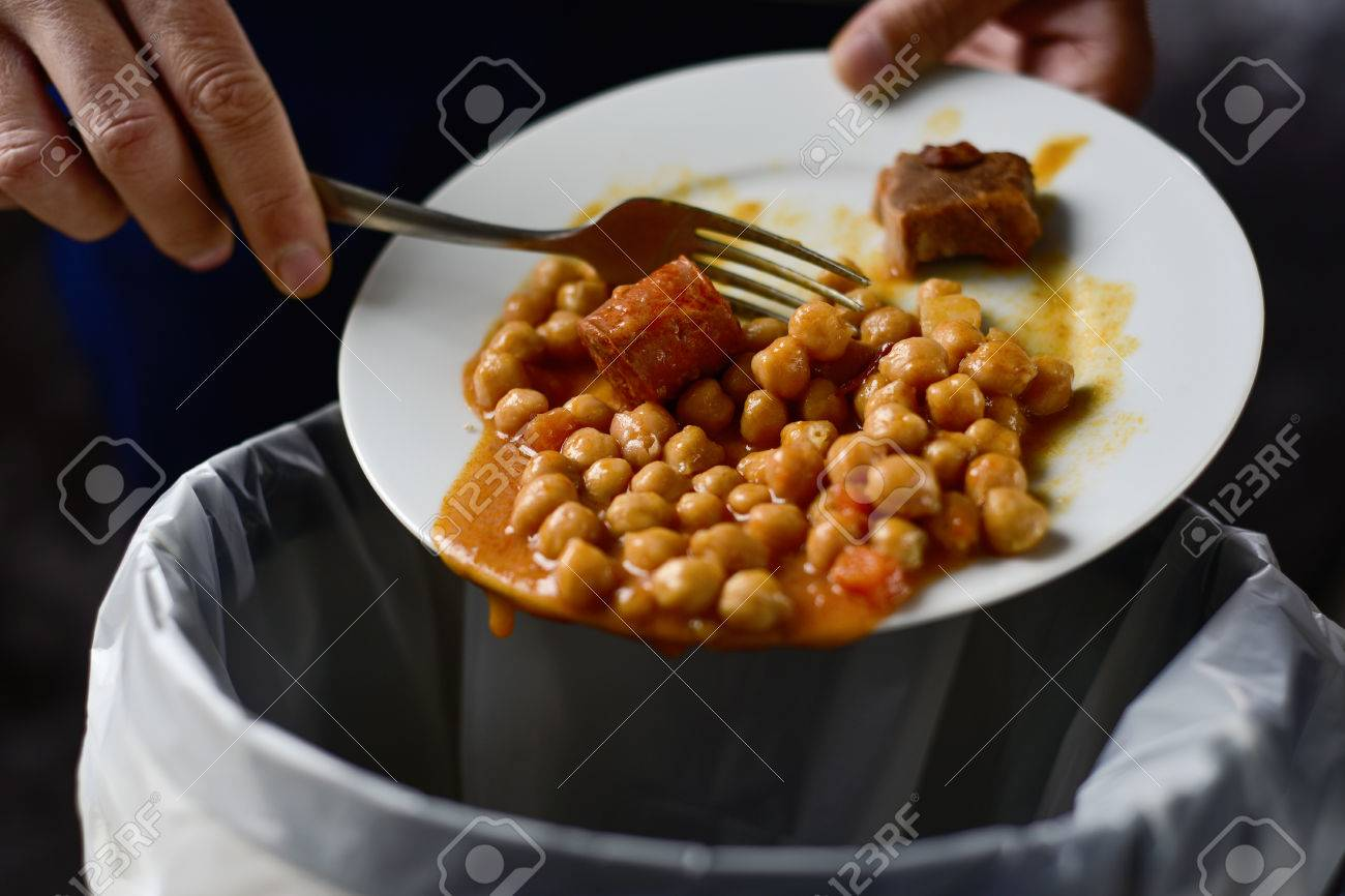 closeup of a young caucasian man throwing the leftover of a plate of chickpea stew to the trash bin Banque d'images - 71176344
