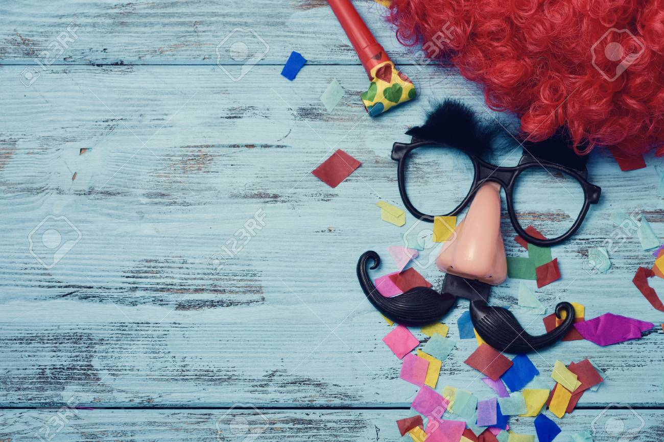 a red wig, a pair of fake black glasses with eyebrows, a nose and a mustache forming the face of a man on a blue rustic wooden surface full of confetti, and a blank space on the left - 71186188