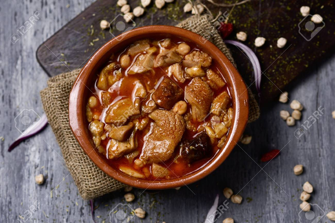 high-angle shot of an earthenware bowl with spanish callos, a typical beef tripe stew with chickpeas, morcilla and chorizo, on a rustic wooden table - 71929084