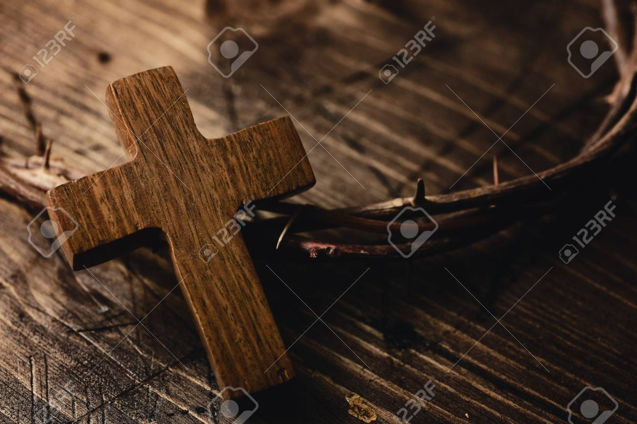 closeup of a small wooden cross and a depiction of the crown of thorns of Jesus Christ on a wooden surface - 72766278
