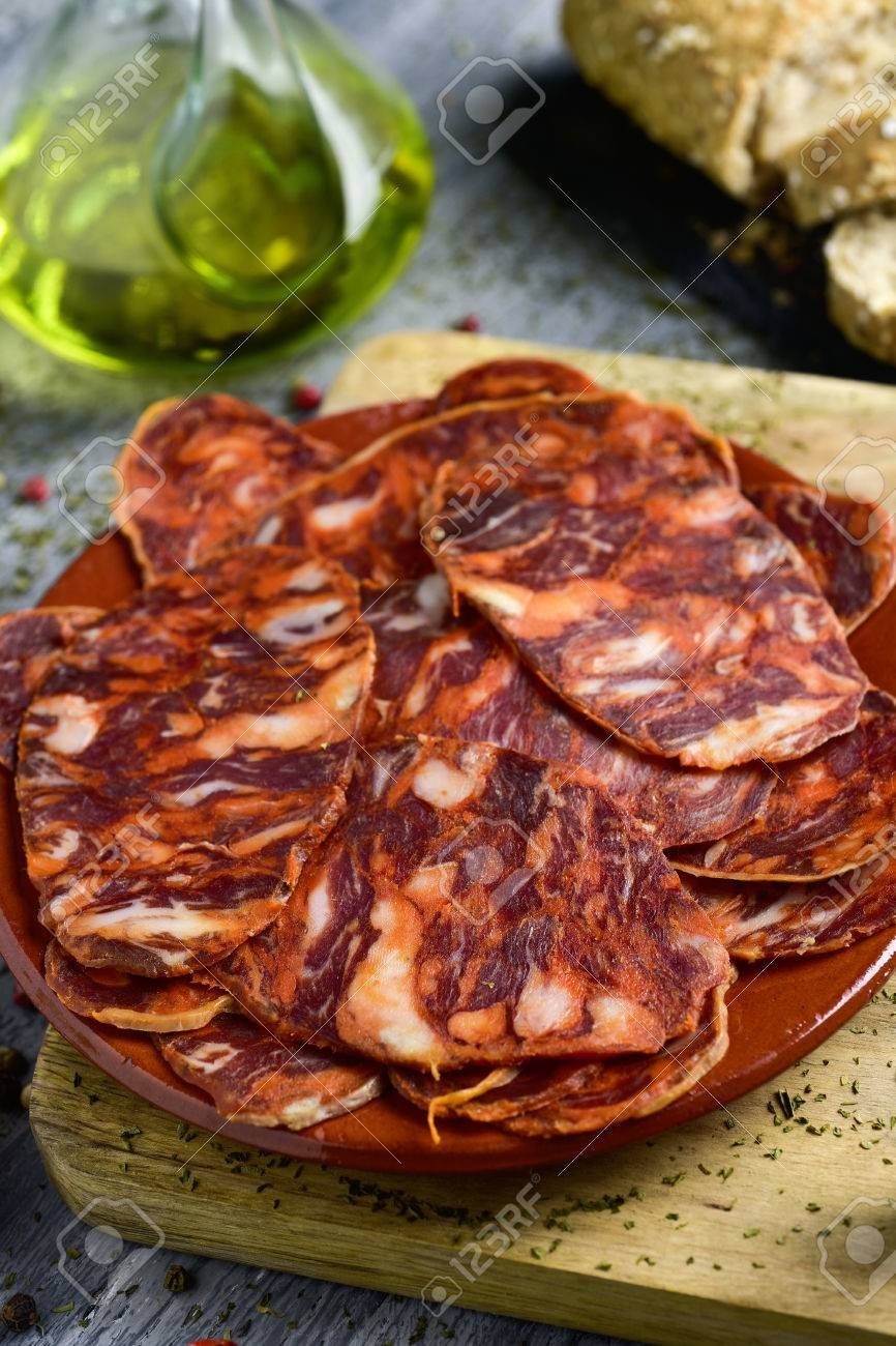 closeup of an earthenware plate with some slices of spanish chorizo, a cured pork sausage, on a rustic wooden table, and some slices of bread and a cruet with olive oil in the background - 72997641