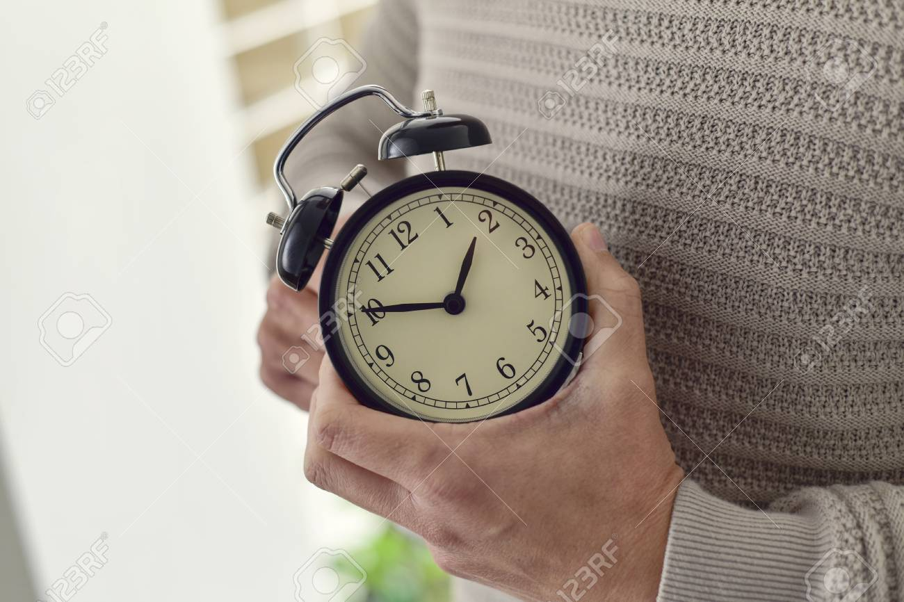 closeup of young Caucasian man winding or adjusting the time of an alarm clock - 73151427