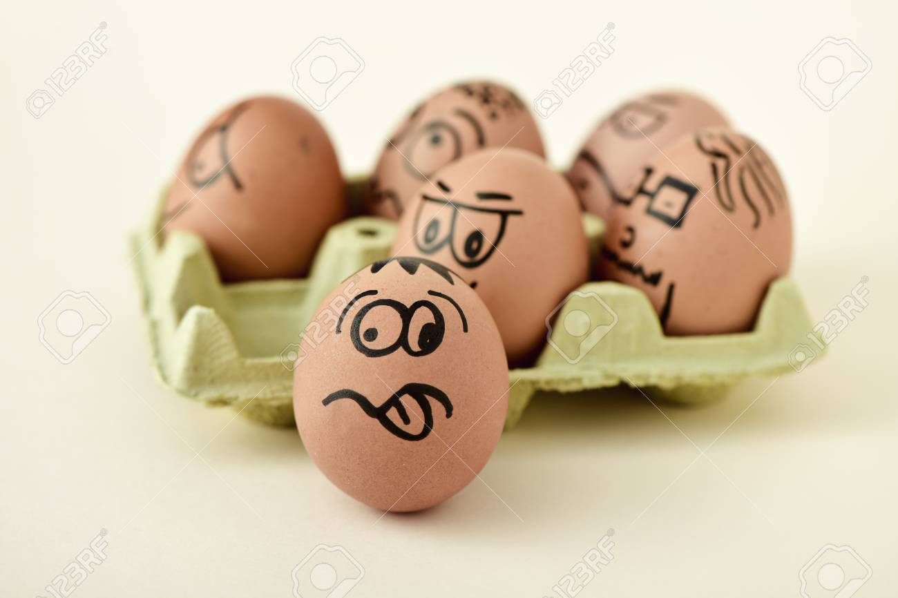 A Pile Of Brown Eggs Ornamented With Funny Faces In Yellow Egg Carton On
