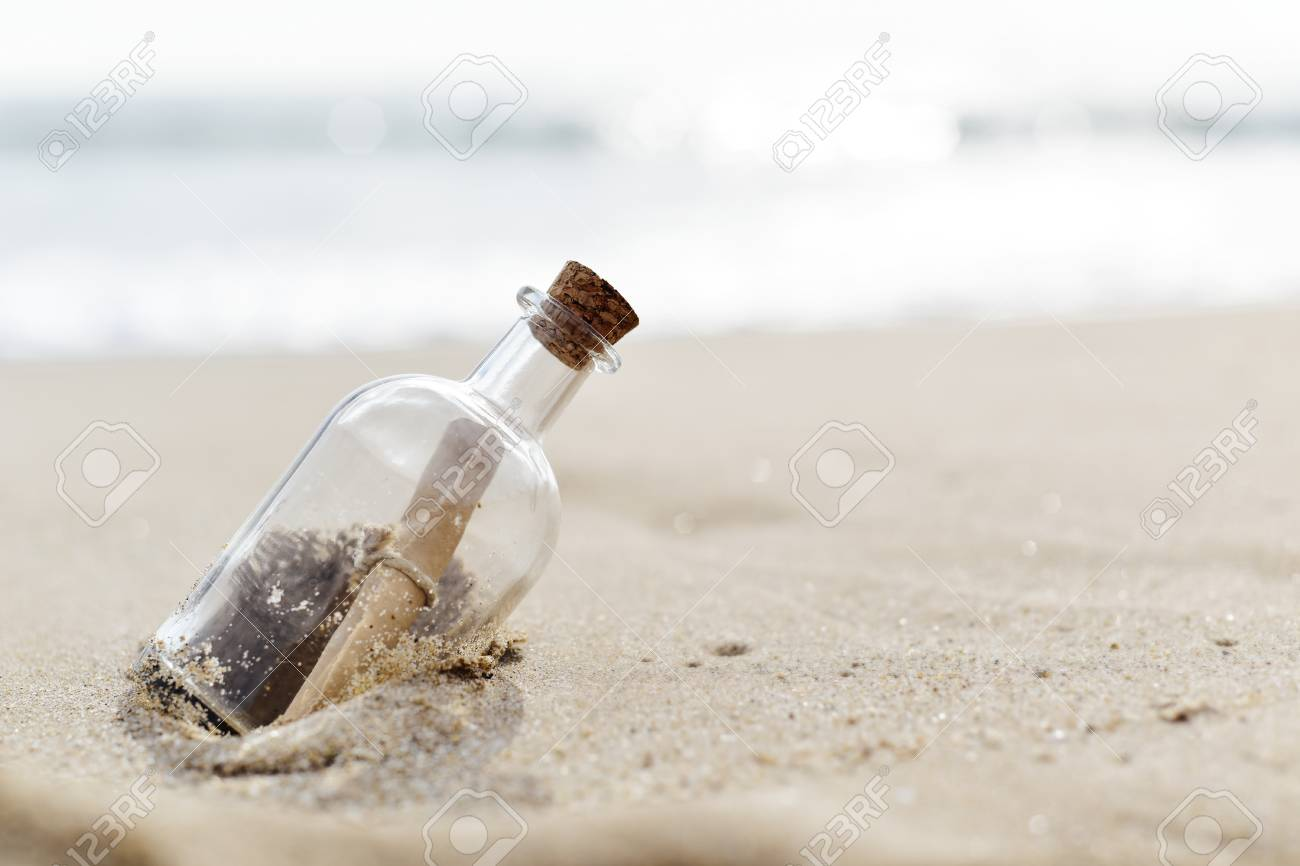 closeup of a glass bottle with a rolled message inside stranded in the sand of a lonely beach - 77153840
