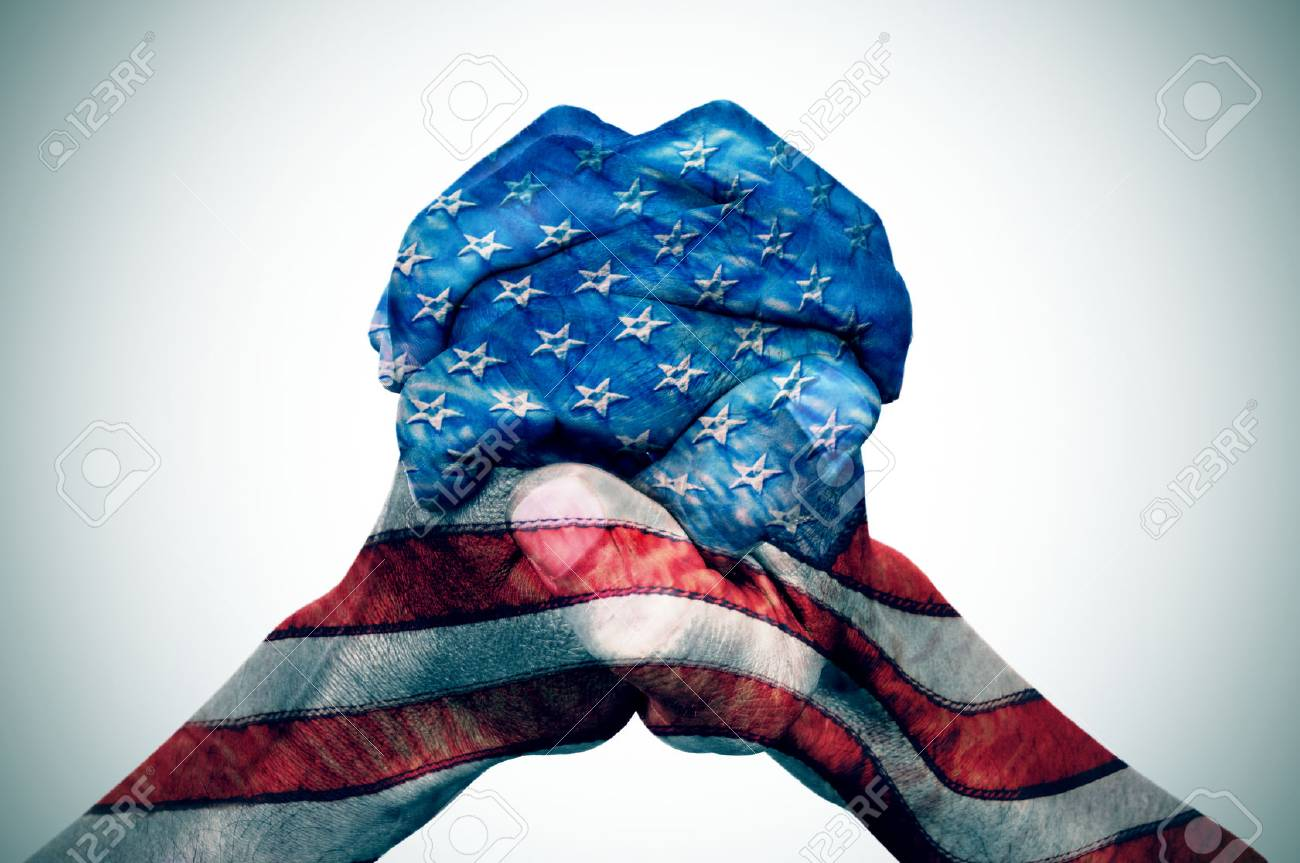 the clasped hands of a young caucasian man patterned with the flag of the United States on an off-white background, with a slide vignette added - 78209041