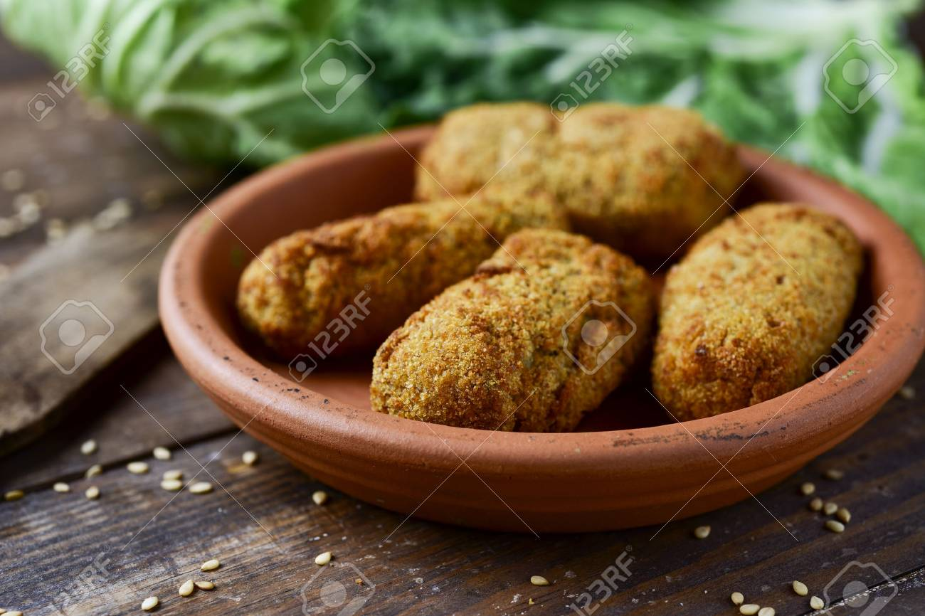 closeup of an earthenware plate with some homemade croquetas, spanish croquettes, on a rustic wooden table - 80629805