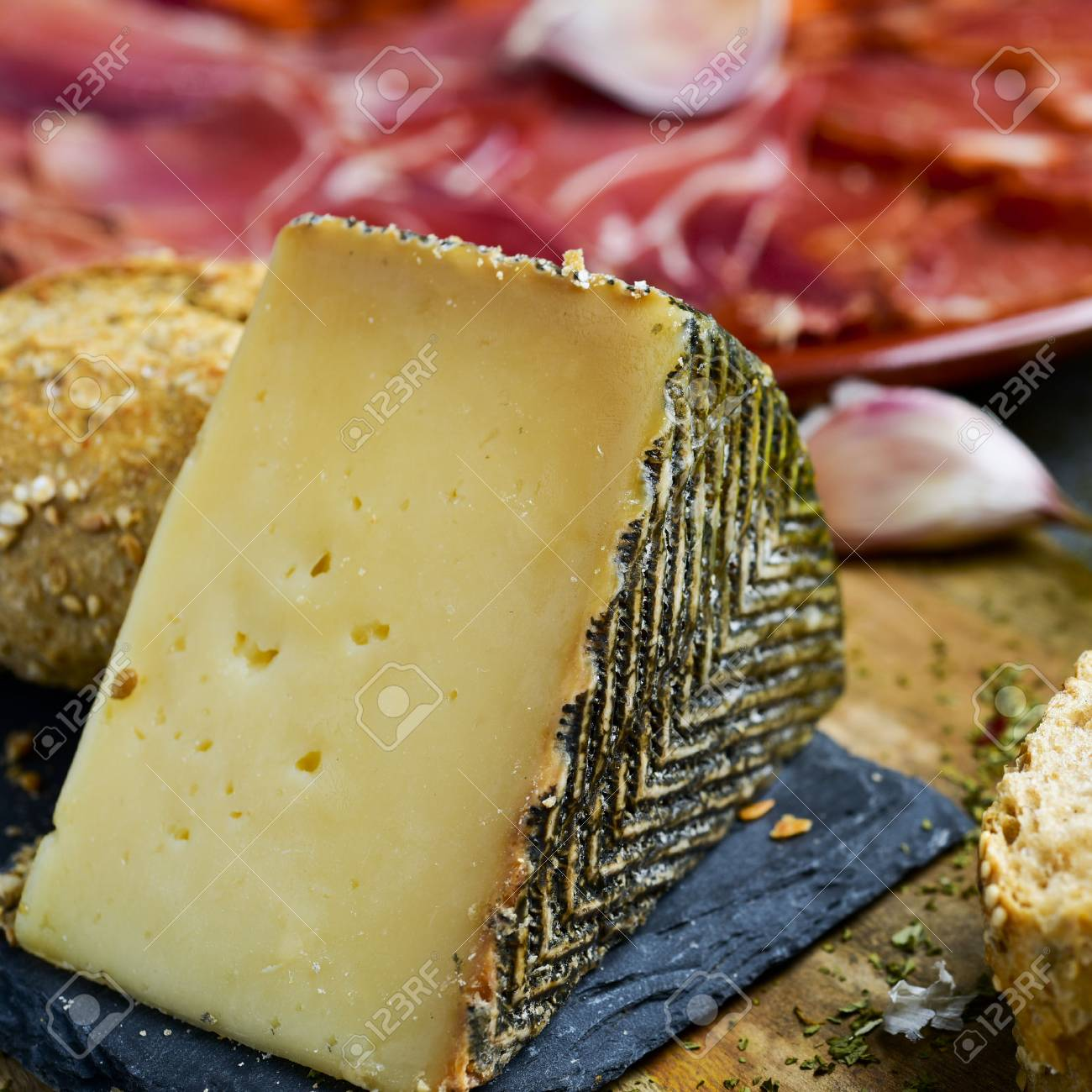 closeup of a piece of manchego cheese, and a plate with an assortment of different spanish cold meats as chorizo, cured pork tenderloin and serrano ham in the background - 80717398