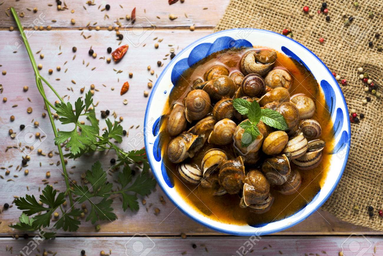 high-angle shot of a ceramic bowl with spanish caracoles en salsa, cooked snails in sauce, on a rustic wooden table - 82819624