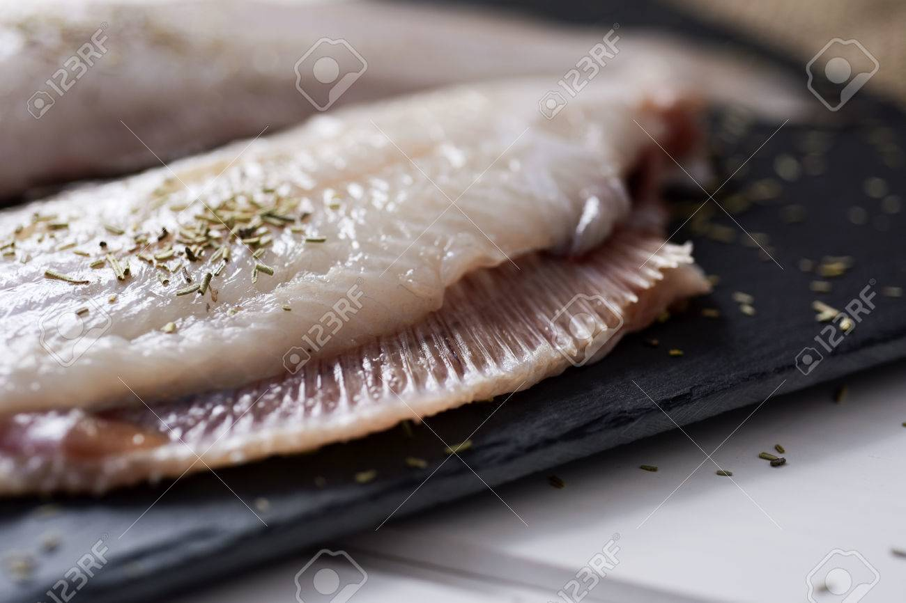 closeup of a pair of raw filleted common sole on a slate tray placed on a rustic wooden table - 82933995