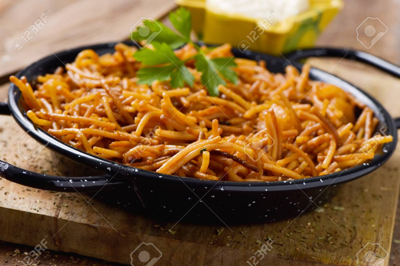 closeup of a spanish fideua, a typical noodles casserole with seafood, in a paella pan and aioli sauce in a yellow mortar on a rustic wooden table - 83022605