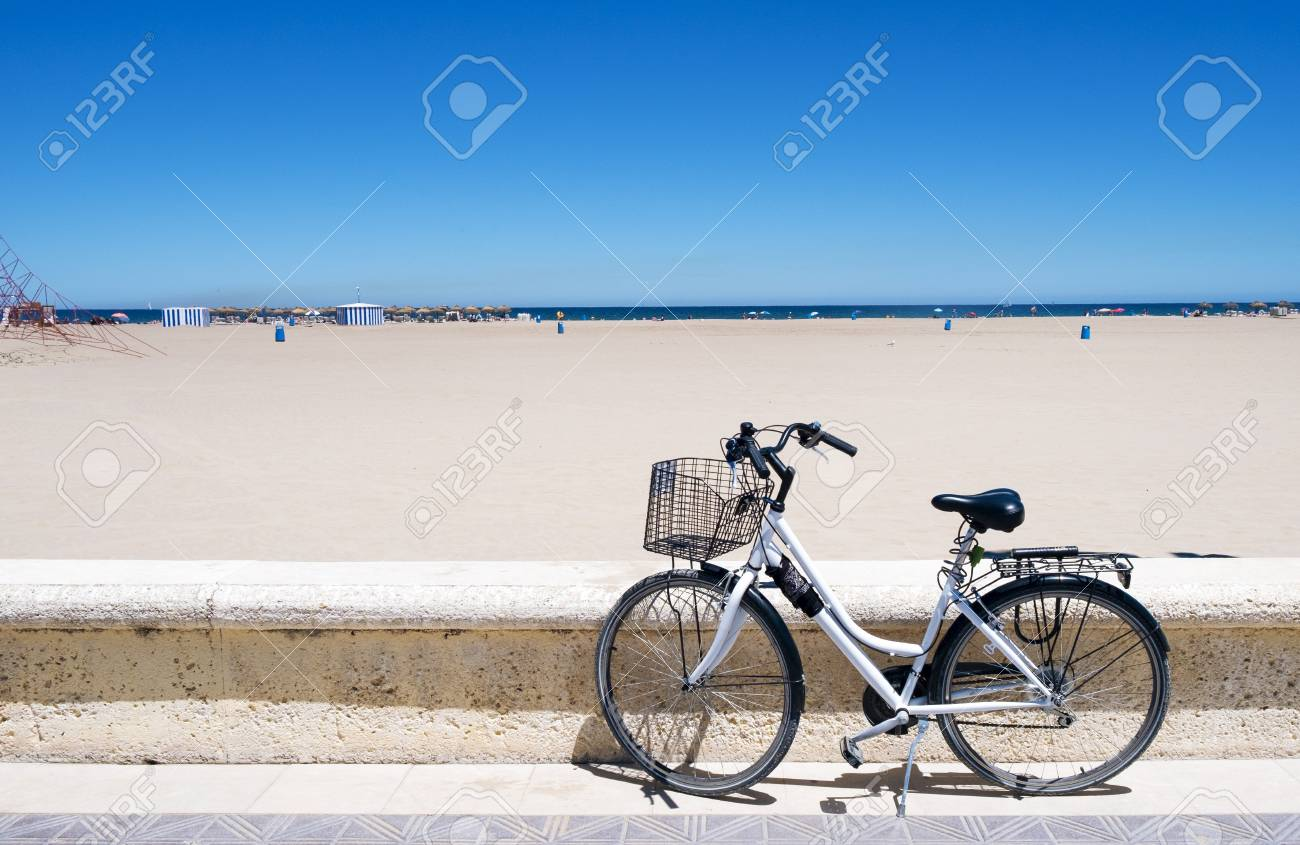 a bicycle parked in the seafront of the popular La Malvarrosa beach, in Valencia, Spain - 84202000