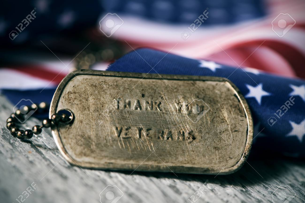 closeup of a rusty dog tag with the text thank you veterans engraved in it, next to a flag of the United States, on a rustic wooden surface - 89751270