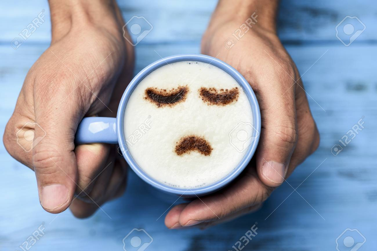 high-angle shot of a young caucasian man with a blue cup of cappuccino with a sad face drawn with cocoa powder on the milk foam, on a blue rustic table - 92801765