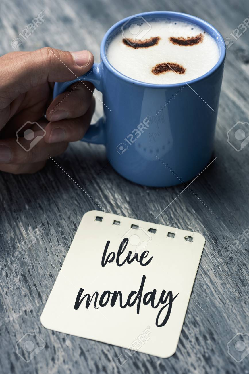 closeup of a note with the text blue Monday written in it on a gray rustic table and a young caucasian man with a blue cup of cappuccino with a sad face drawn with cocoa powder on its milk foam - 92990910