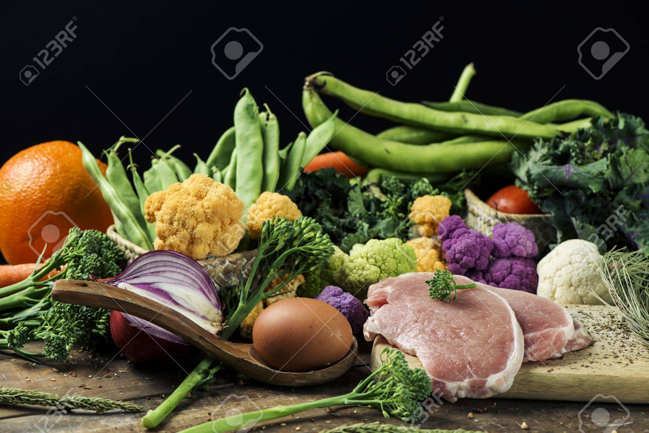 a pile of some fruit and some different raw vegetables, such as cauliflower of different colors, broccolini or french beans, and some eggs and some slices of meat on a rustic wooden table - 95725126