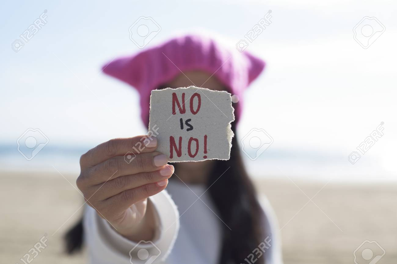 closeup of a young caucasian woman outdoors wearing a pink hat showing a piece of paper in front of her face with the text no is no written in it - 95972510