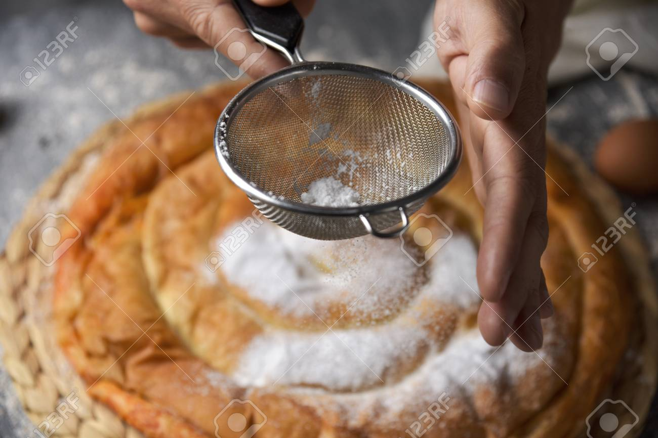 closeup of a young caucasian man sprinkling powdered sugar on an ensaimada, a pastry typical of Mallorca, Spain, placed on a rustic wooden table - 97242725