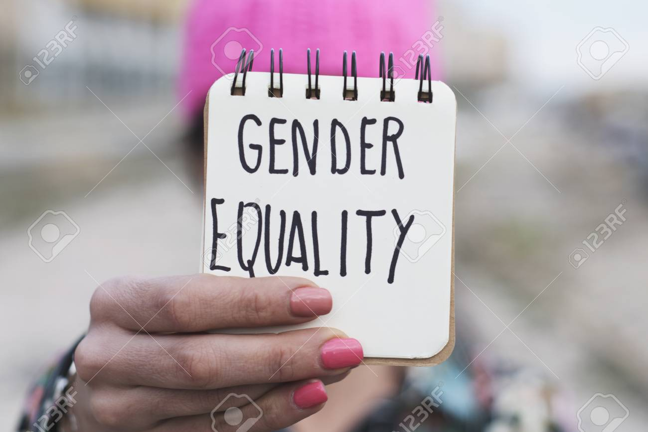 closeup of a young woman outdoors wearing a pink pussycat hat showing a notepad in front of her face with the text gender equality written in it - 98825295
