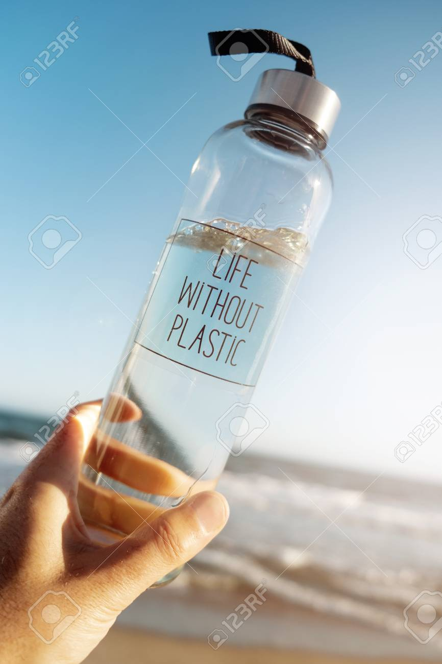 Closeup of a caucasian man holding a glass reusable water bottle with the text life without plastic written - 119130256
