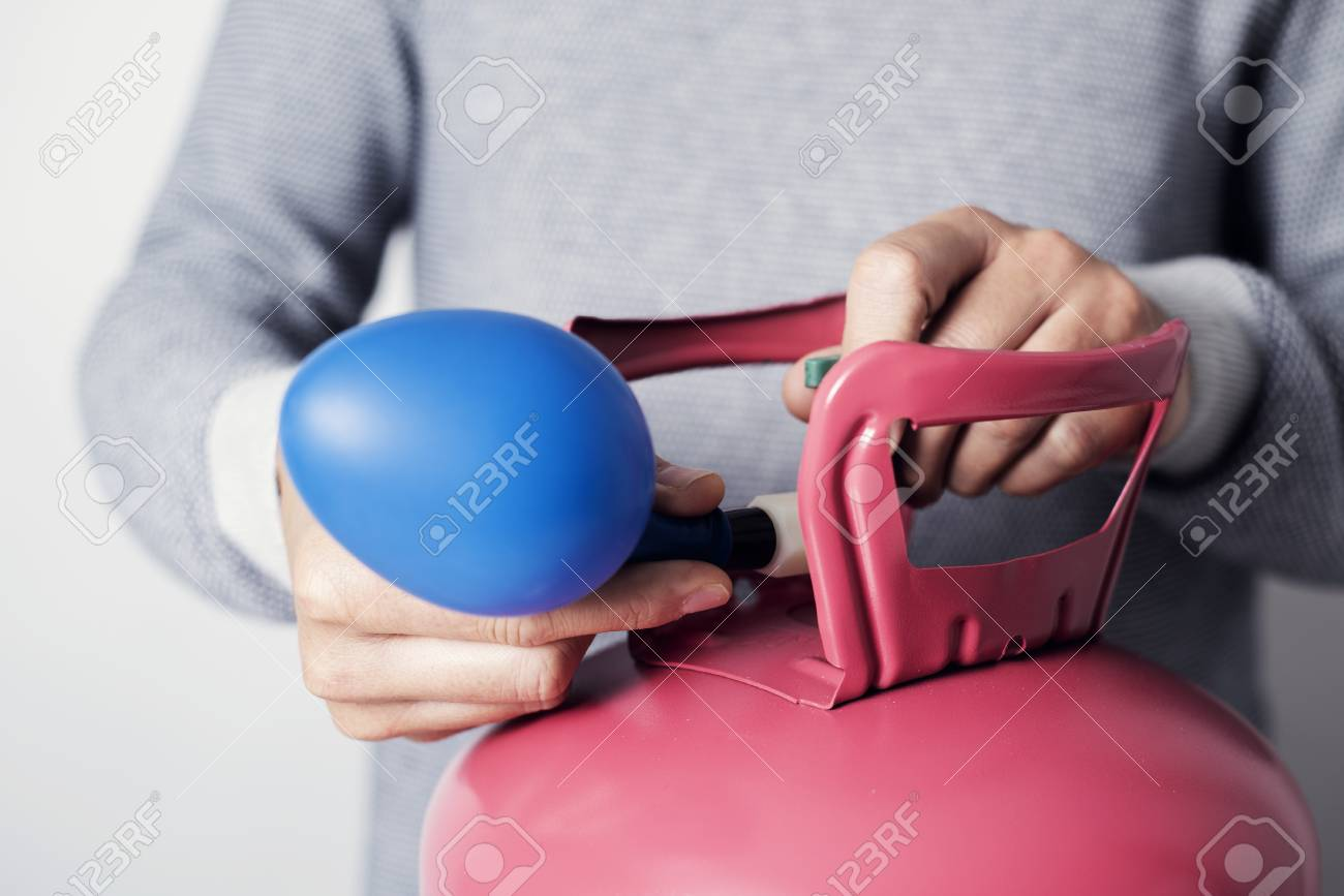 Closeup of a caucasian man, wearing a gray sweater, inflating a blue balloon with helium from a pink cylinder - 119130269