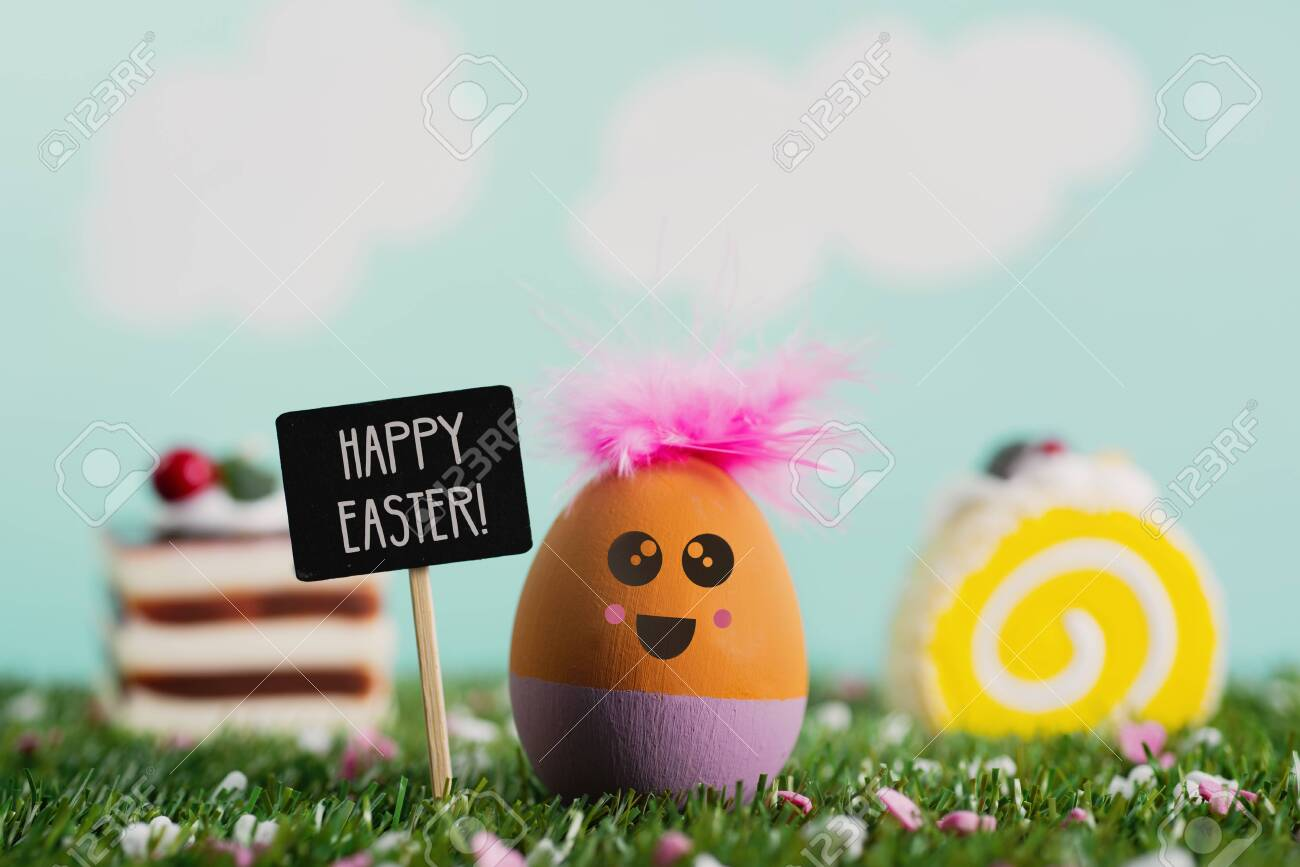 a handmade easter egg, with a cute face, on the grass, next to a black signboard with the text happy easter written in it, some pieces of colorful cakes and a sky with clouds in the background - 120706258