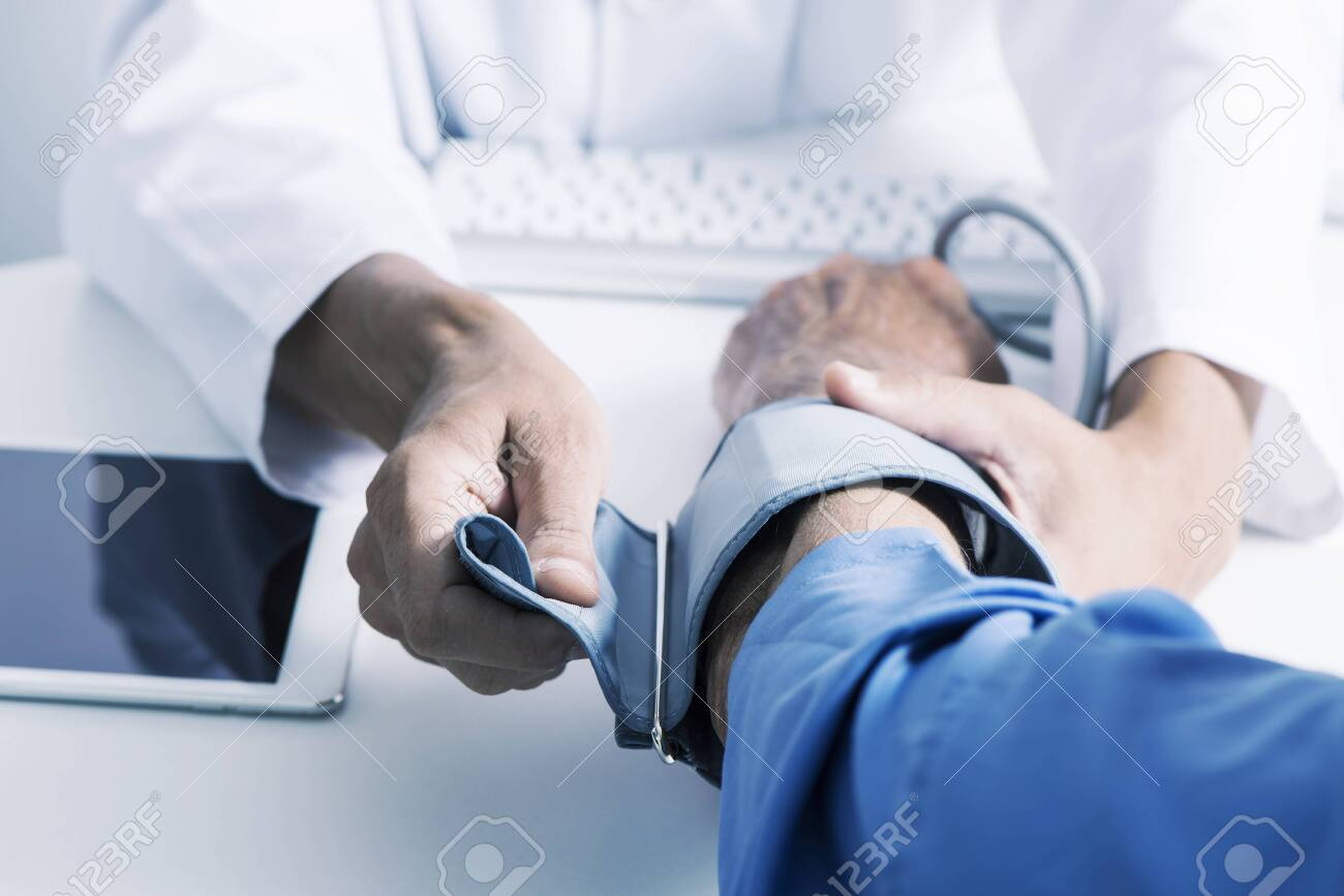 closeup of a caucasian doctor man, in a white coat, about to measure the blood pressure of a senior caucasian patient man with a sphygmomanometer, sitting both at the doctors desk - 121677878