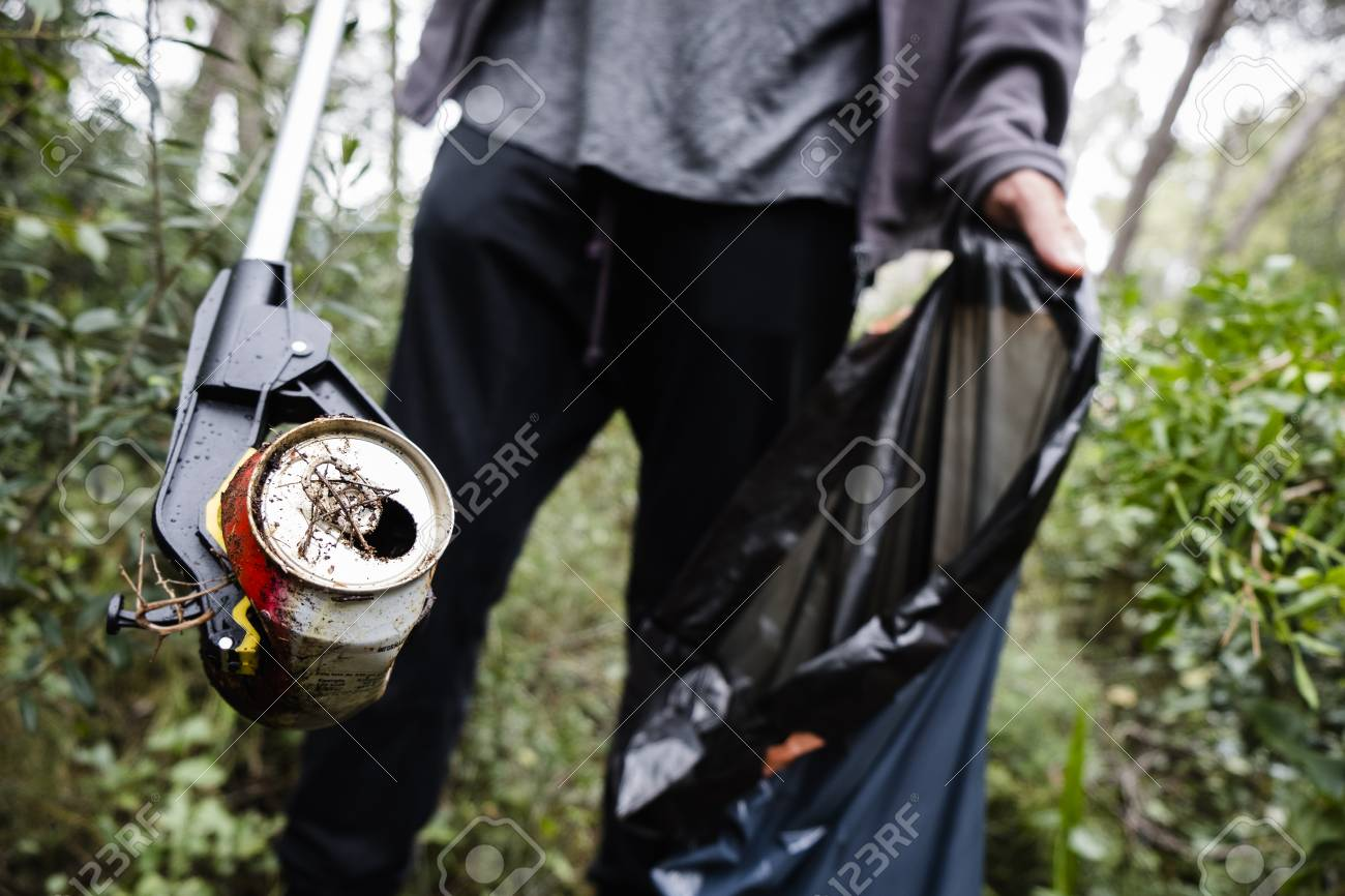 closeup of a caucasian man collecting garbage with a trash grabber stick, in a forest, as an action to clean the natural environment - 124668925