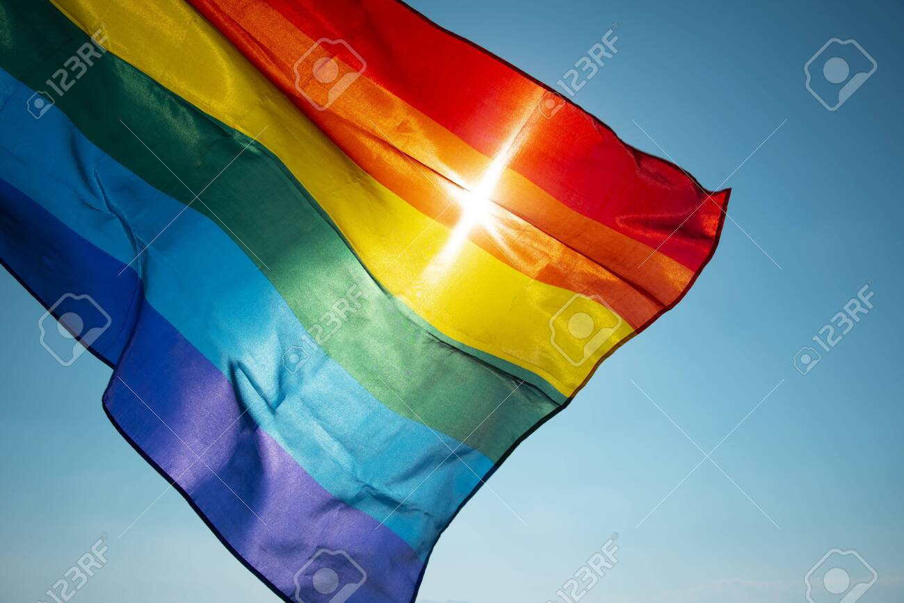 closeup of a rainbow flag waving on the blue sky, moved by the wind, with the sun in the background - 125571032