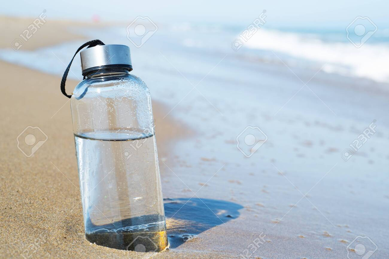 closeup of a glass reusable water bottle on the seashore of a lonely beach - 126018623