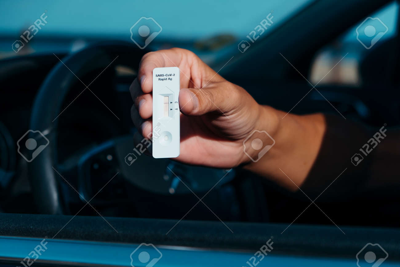 a young caucasian man, sitting in the driver seat of his car, shows a test device with a negative result - 173023191
