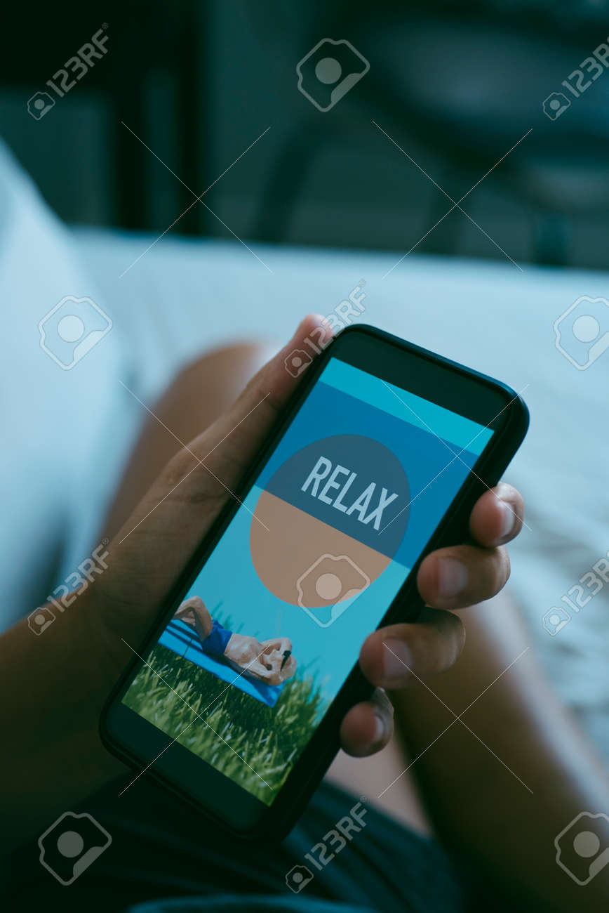 closeup of a young caucasian man resting sitting on bed while is looking at his smartphone, that reads relax in its screen - 172883192