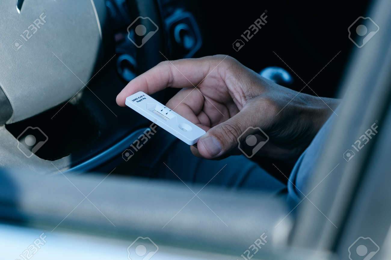 closeup of a young man, in a casual wear, looking to an antigen diagnostic test device, waiting for the results, while is sitting in the driver seat of his car - 173023204