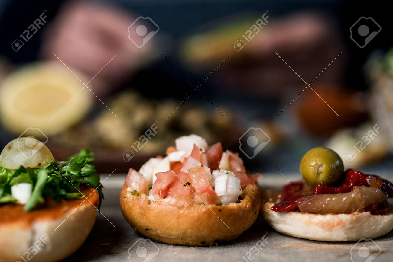 closeup of some vegan sandwiches, with different toppings, such as roasted vegetables or raw chopped tomato and onion, to eat as snacks or appetizers, and a man preparing some more in the background - 173023206
