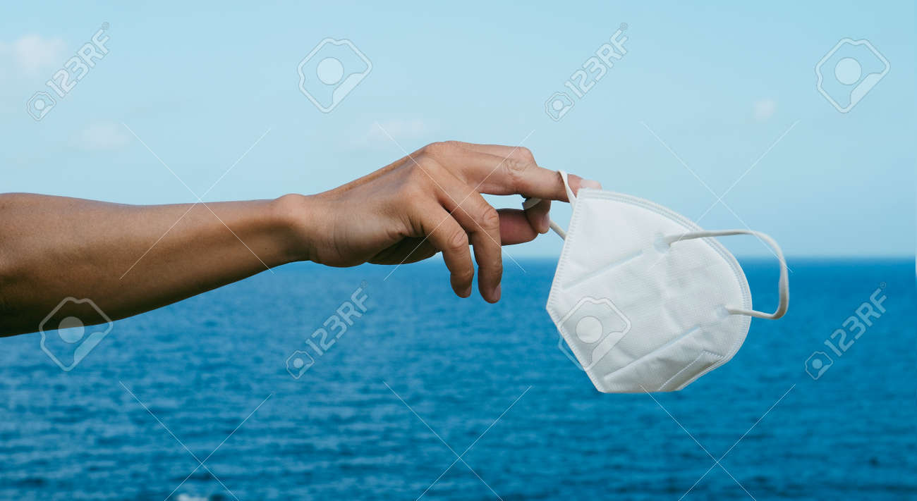 a young caucasian man holds a white FFP2 face mask in his hand in front of the ocean, as he is taking a breather of wearing it, in a panoramic format to use as web banner or header - 173023232