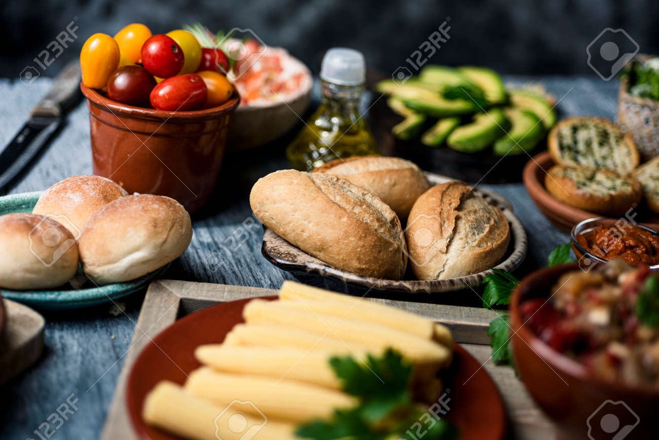 closeup of some different ingredients on a table to prepare vegan sandwiches or appetizers, such as different bread buns, cooked baby corns, cherry tomatoes, avocado or olive oil - 173023237