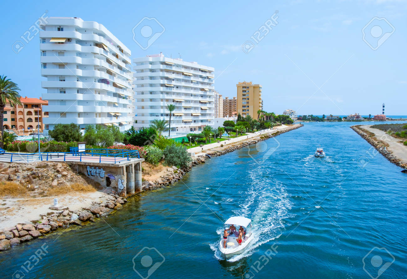 LA MANGA, SPAIN - JULY 29, 2021: View of the Gola del Puerto canal in La Manga del Mar Menor, Murcia, Spain, that connects the lagoon and the Mediterranean sea, and the Estacio lighthouse on the right - 173421018