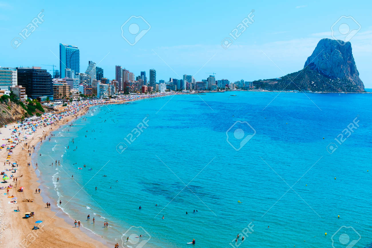 CALPE, SPAIN - AUGUST 2, 2021: A panoramic view over the main beach of Calpe, in the Valencian Community, highlighting its characteristic apartment towers and the Penon de Ifac promontory on the right - 173421027