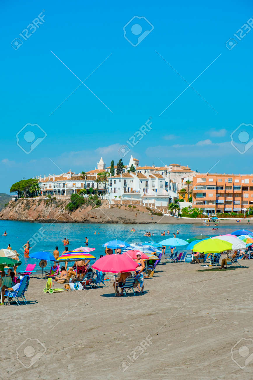 AGUILAS, SPAIN - JULY 29, 2021: Some people enjoy the beach in Calabardina Beach, in Aguilas, in the Costa Calida coast, in the Region of Murcia, Spain - 173421056