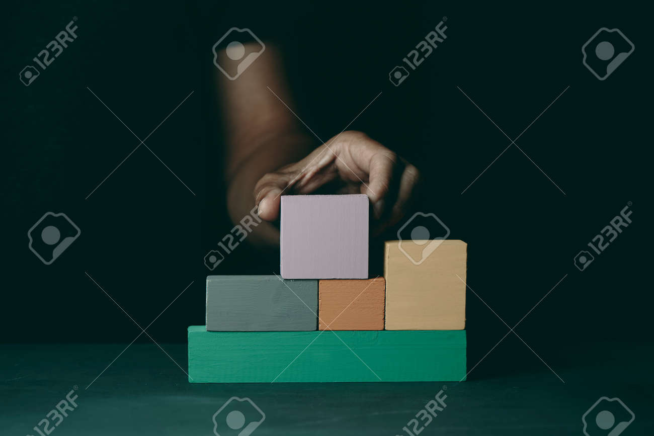 a caucasian man builds a structure with some wooden toy blocks of different colors, on a dark gray surface - 173345566