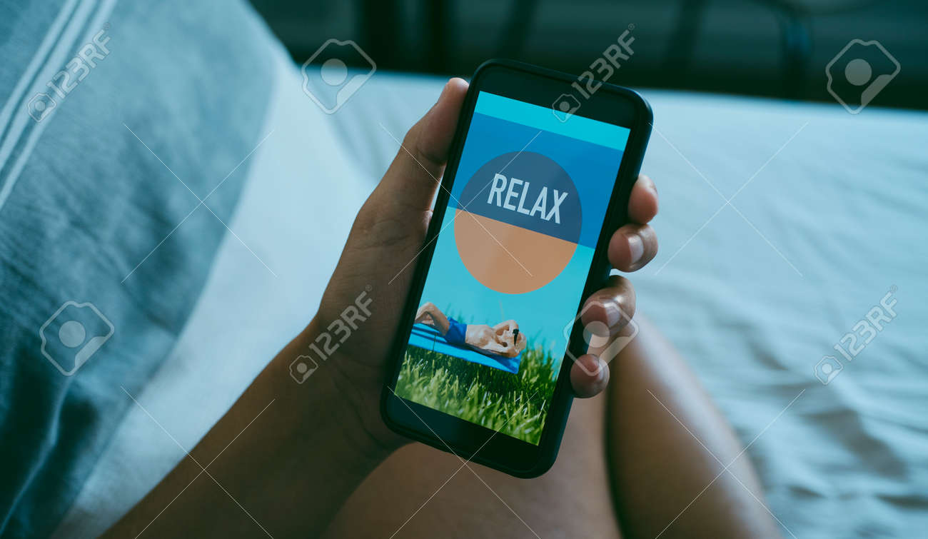 a young caucasian man is sitting comfortably on bed while is looking at his smartphone, that reads relax in its screen, in a panoramic format to use as web banner or header - 173345629
