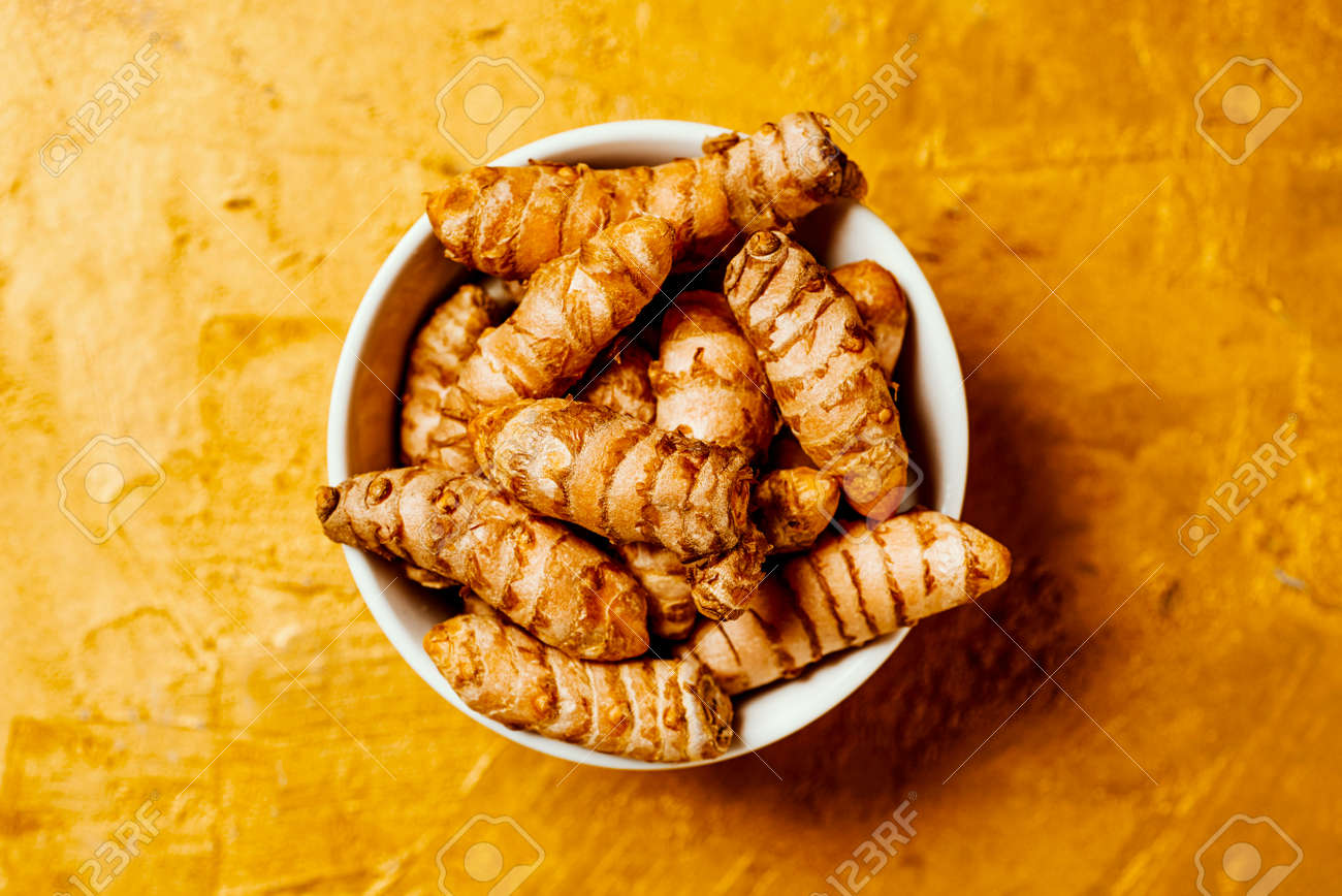 high angle view of some turmeric roots, curcuma longa species, in a ceramic bowl placed on a golden textured surface - 173411661