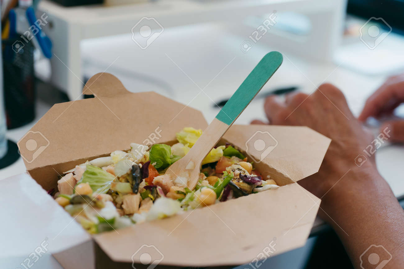 closeup of a chickpea salad served in a paper container on a desk next to a young caucasian man using his computer - 173345588