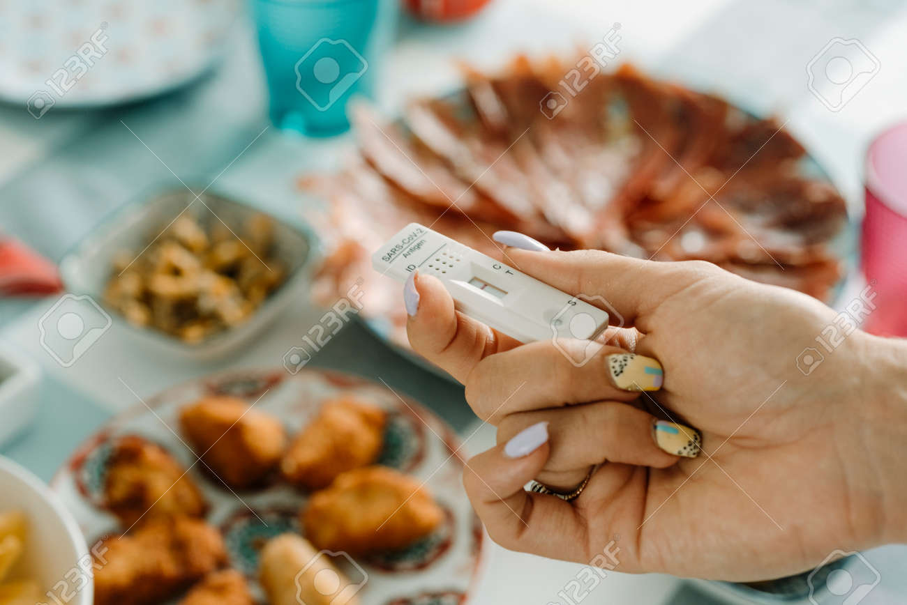 a young caucasian woman has a covid-19 antigen diagnostic test device with a negative result in her hand, sitting at a table set for lunch - 173411663