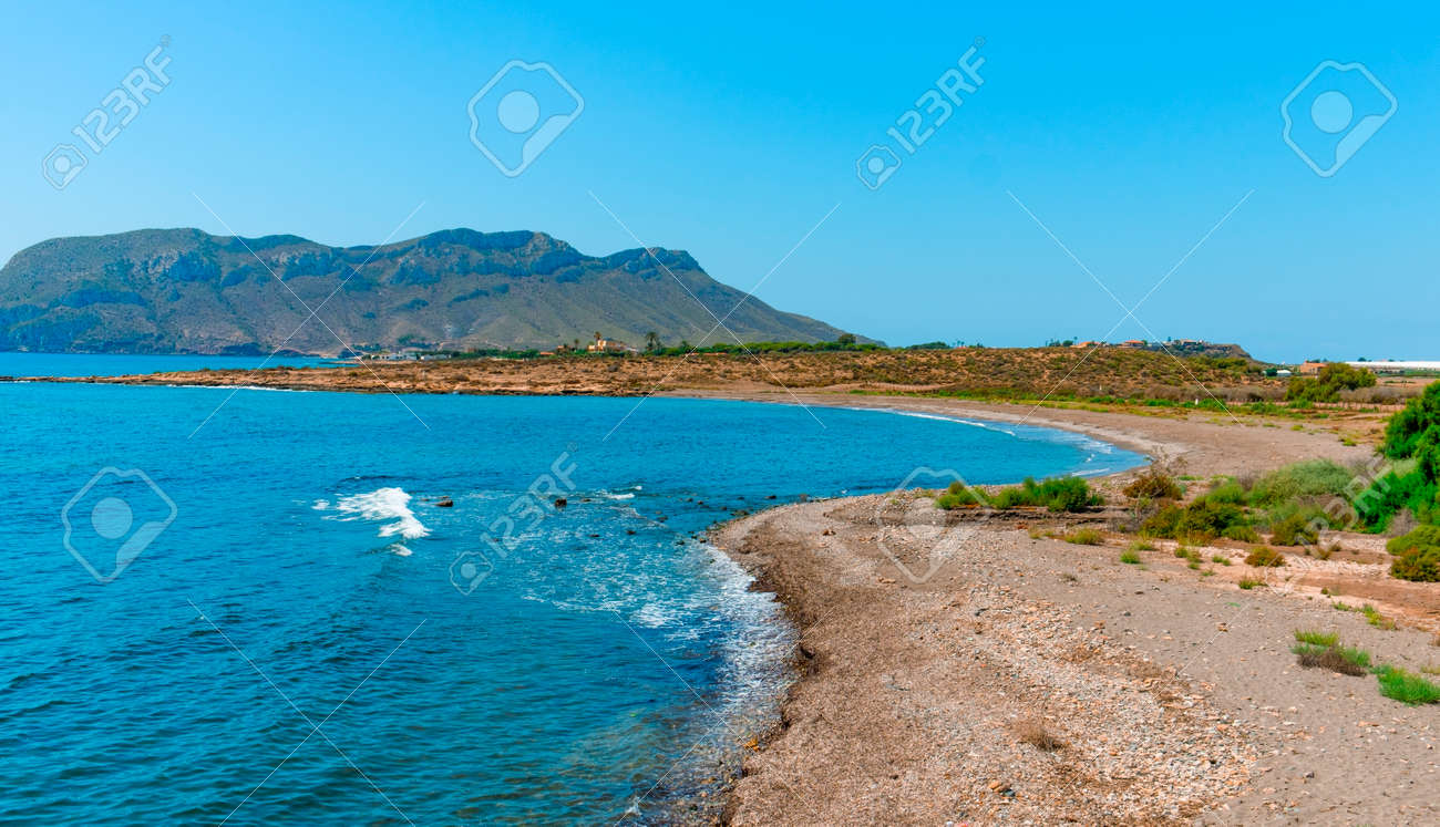 a panoramic view over the lonely El Rafal beach, in Aguilas, in the Costa Calida coast, Region of Murcia, Spain, with the mountain of the Cope cape in the background - 173404306