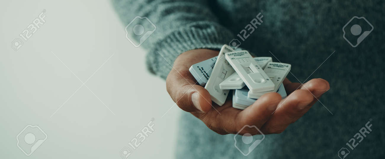 closeup of a young man with a bunch of covid-19 antigen diagnostic test devices in his hand, in a panoramic format to use as web banner or header - 173411684