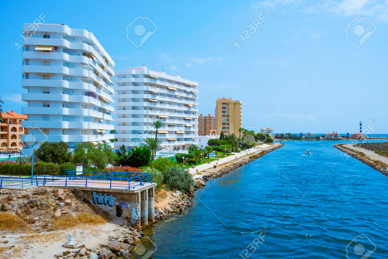 La Manga, Spain - July 29, 2021: A view of the Gola del Puerto canal in La Manga del Mar Menor, Murcia, Spain, connecting the lagoon and the Mediterranean sea, and the Estacio lighthouse on the right - 173480962