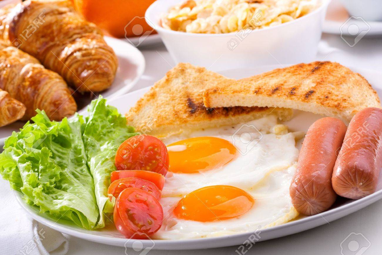 breakfast with fried eggs, sausages, tomatoes and toasts Stock Photo - 13654215