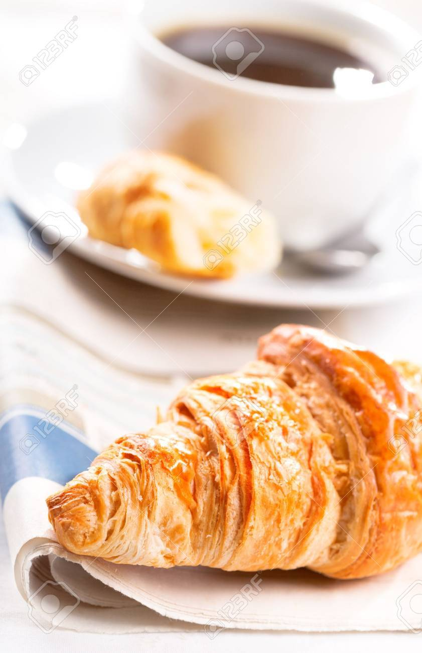 breakfast with croissant, cup of black coffee and newspaper Stock Photo - 16409454